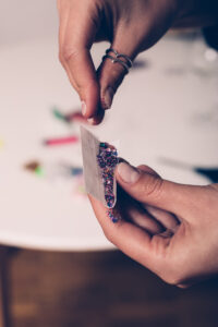 hands rooling tobacco paper with glitter inside PGB4V9C scaled